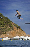 Boy jumping off diving board. Boy makes acrobatic leap off diving board into Mediterranean cove with moored boats and pine-clad cliffs in the background Royalty Free Stock Images