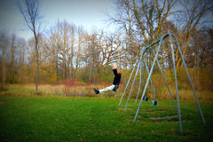 Boy Jumping Off Swing. A young boy getting ready to jump off of a swing in a park at Big Foot Beach State Park in Lake Geneva, WI located in Walworth County stock image