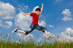 Boy jumping outdoor. Boy jumping on green meadow against blue sky Royalty Free Stock Photos