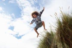 Boy jumping over dune. Having fun royalty free stock photos