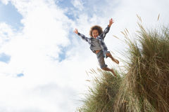 Boy jumping over dune. Having fun stock images