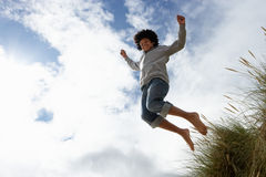 Boy jumping over dune. Smiling stock photography