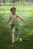 Boy jumping over lawn sprinkler Stock Photos
