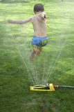 Boy jumping over lawn sprinkler Royalty Free Stock Photo