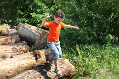 Boy Jumping Over Logs Stock Image