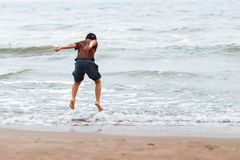 Boy jumping over the sea waves Royalty Free Stock Photography