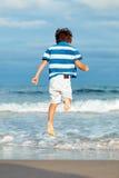 Boy jumping over waves Stock Photos