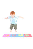 Boy jumping over word jump. Young boy jumping over word jump. Isolated on white Stock Photos
