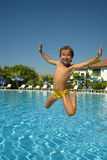 Boy jumping into the pool. Smiling Stock Photography