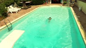 Boy jumping into the pool. Boy diving and swimming into pool stock video