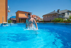 Boy jumping in the pool Royalty Free Stock Photo