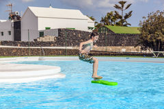 Boy jumping in the pool. With the surfboard Royalty Free Stock Images
