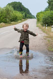 Boy jumping in puddles Royalty Free Stock Image