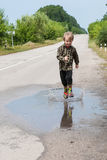 Boy jumping in puddles Stock Image