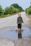 Boy jumping in puddles Stock Photos