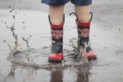 Boy Jumping in Rain Puddle Royalty Free Stock Photos