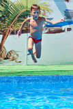 Boy jumping into resort pool Royalty Free Stock Images