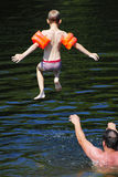 Boy jumping into the river Royalty Free Stock Image