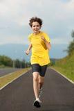 Boy running outdoor. Boy jumping on running lane against blue sky Stock Photos