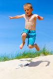 Boy jumping from a sand dune Stock Photos