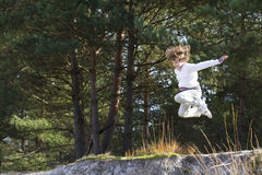 Boy jumping from sand dunes in pinewood forest. On autumn day Royalty Free Stock Photography