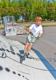 Boy is jumping with scooter in a skatepark Stock Photos