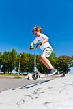 Boy is jumping with scooter in a skatepark Royalty Free Stock Images
