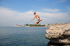 Boy jumping into the sea from the old pier, Vladivostok. Boy jumping into the sea from the old pier. Embankment in Vladivostok, Russia Royalty Free Stock Photography