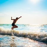 Boy Jumping In Sea Waves Stock Photography