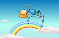 A boy jumping in the sky and a rainbow Stock Photography