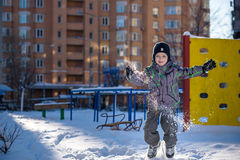 Boy jumping in snow. Happy kid walking outdoors in winter city. Child smiling and having fun. Stock Image