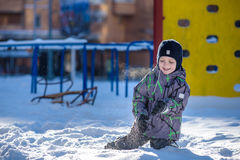 Boy jumping in snow. Happy kid walking outdoors in winter city. Child smiling and having fun. Stock Images
