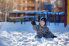 Boy jumping in snow. Happy kid walking outdoors in winter city. Child smiling and having fun. Royalty Free Stock Photo