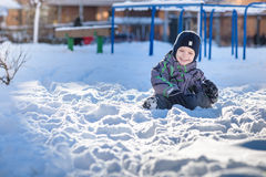 Boy jumping in snow. Happy kid walking outdoors in winter city. Child smiling and having fun. Royalty Free Stock Photos