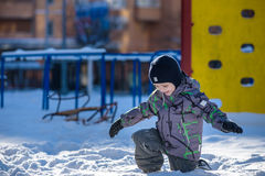 Boy jumping in snow. Happy kid walking outdoors in winter city. Child smiling and having fun. Stock Photos
