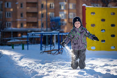 Boy jumping in snow. Happy kid walking outdoors in winter city. Child smiling and having fun. Royalty Free Stock Image