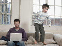 Boy Jumping On Sofa While Father Using Laptop At Home. Playful boy jumping on sofa while father using laptop at home stock image