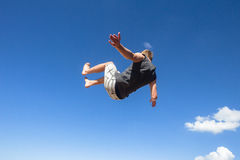 Boy Jumping Somersault Blue Sky Parkour. Teen boy jumping somersault off wall in blue sky on beach park hour Royalty Free Stock Photo