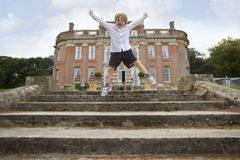 Boy (8-10) jumping on steps by manor house (blurred motion) Royalty Free Stock Image