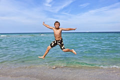 Boy is jumping in the surf of the ocean Stock Photos