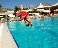 Boy jumping into swimming pool. Boy jumping into blue swimming pool in resort Royalty Free Stock Images