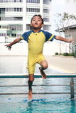 Boy Jumping Into Swimming Pool. A boy jumping from a metal rail into a swimming pool Stock Images