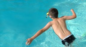 Boy jumping into swimming pool Royalty Free Stock Images