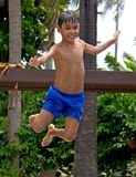 Boy jumping into a swimming pool. Young boy smiling and jumping into a swimming pool Stock Image