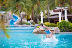 Boy jumping in swimming pool. Happy teenager boy jumping in a swimming pool playing with his father enjoying summer vacation in a beautiful tropical resort Stock Images