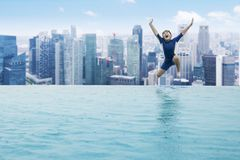 Boy jumping into a swimming pool. JAKARTA - Indonesia. December 26, 2017: Little child jumping into a swimming pool on the rooftop of hotel in Jakarta Stock Photo