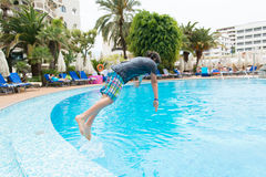 Boy jumping into swimming pool. Boy T-shirt jumping in the pool, in the background a hotel and relax by the pool people Stock Photos