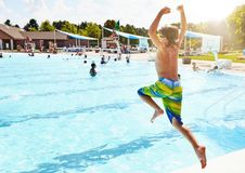 Boy jumping in swimming pool. Travel concept Stock Photography