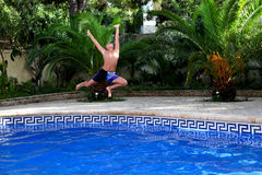 A  boy is jumping into a swimming pool. You can have so much fun splashing and playing in the swimming pool in hot weather of spanish summer Royalty Free Stock Photos