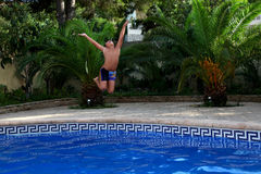 A boy is jumping into a swimming pool. You can have so much fun splashing and playing in the swimming pool in hot weather of spanish summer Royalty Free Stock Photography